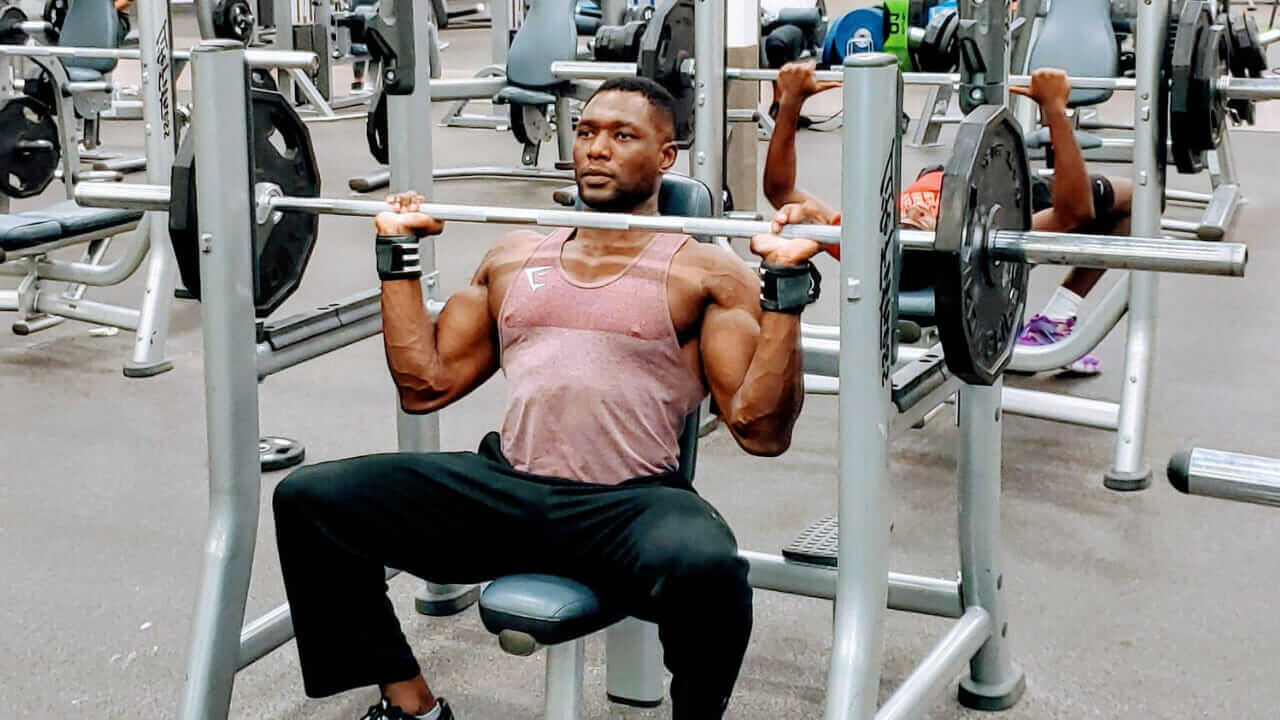 Nurudeen Tijani working out shoulder and arms doing shoulder press with barbell in gym